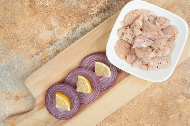 Ungekochte hähnchenschenkel in weißem teller mit geschnittenen zwiebeln.