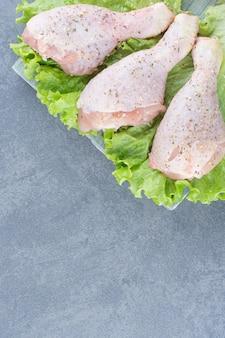 Ungekochte hähnchenschenkel mit salat auf holzbrett.