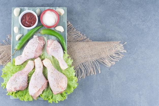 Ungekochte hähnchenschenkel und chilischoten auf holzbrett.