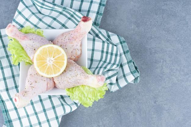 Ungekochte hähnchenschenkel und zitronenscheibe in weißer schüssel.