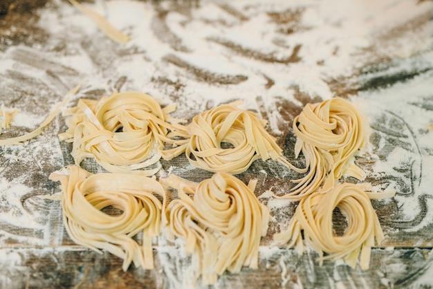 Ungekochte hausgemachte fettuccine auf hölzernem küchentisch mit mehl-nahaufnahme bestreut. frische pastazubereitung