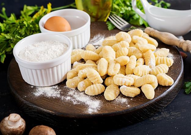 Ungekochte hausgemachte gnocchi mit champignonrahmsauce und petersilie