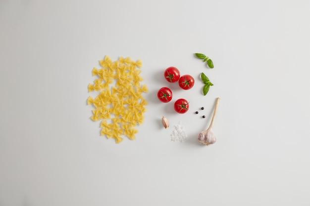 Ungekochte, hochwertige farfalle-nudeln in fliegenform, zutaten für die zubereitung eines italienischen gourmetgerichts aus hartem hartweizenmehl. zähe und schmackhafte pasta. große energiequelle