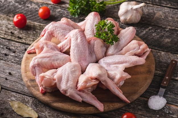 Ungekochte hühnerflügel auf gewürzen eines hölzernen schneidebretts. nahansicht