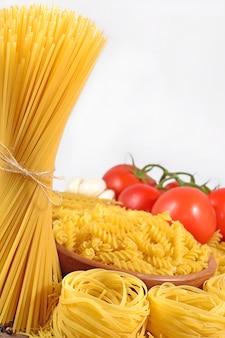 Ungekochte italienische pasta und reife tomaten verzweigen sich auf weißem hintergrund