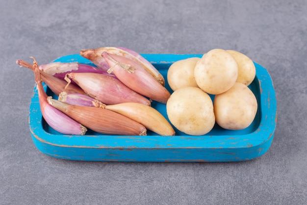 Ungekochte kartoffeln mit knoblauch in einem blauen holzbrett.
