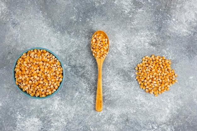 Ungekochte maiskörner in blauer schüssel auf marmoroberfläche.