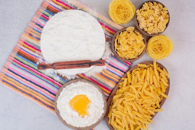 Ungekochte makkaroni auf holzschalen mit eigelb und mehl.