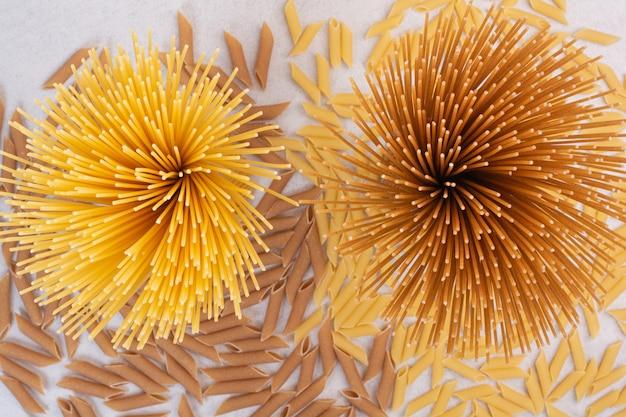 Ungekochte makkaroni mit frischen rohen nudeln auf weißem raum.