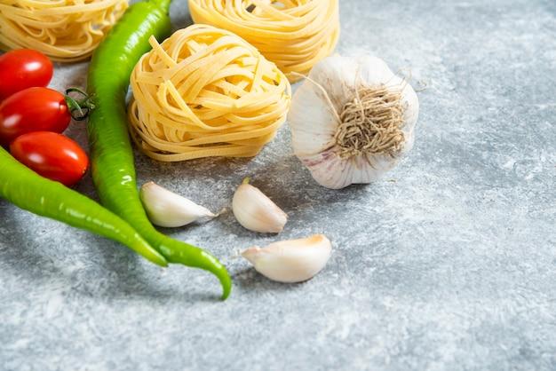 Ungekochte nest-spaghetti mit gemüse auf marmorhintergrund