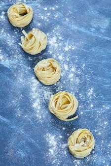 Ungekochte nester von tagliatelle-nudeln isoliert.
