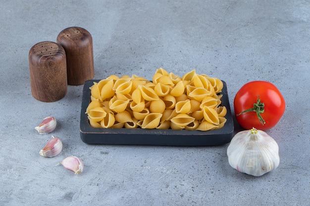 Ungekochte nudeln in einem brett mit frischen roten tomaten und knoblauch schälen.