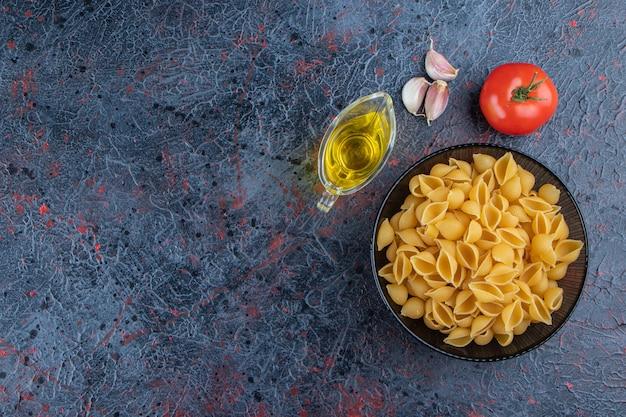 Ungekochte nudeln in einer glasschüssel mit frischen roten tomaten und knoblauch schälen.