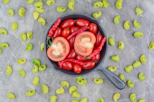 Ungekochte nudeln mit kirschtomaten und chilis in einer schwarzen pfanne