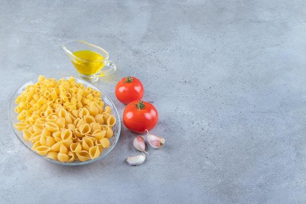 Ungekochte nudeln mit rohem trockenem ditali rigati in einer glasschüssel mit frischen roten tomaten und knoblauch schälen.