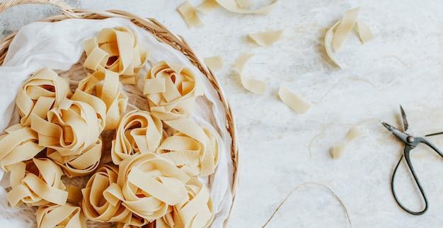 Ungekochte pappardelle-nudeln auf einem holzkorb