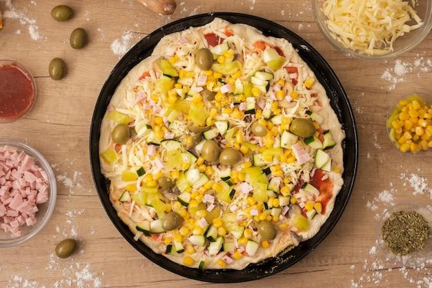 Ungekochte pizza der draufsicht in der wanne mit bestandteilen