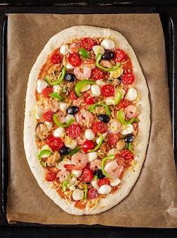 Ungekochte pizza zum backen auf einem blech zum backen zubereitet. italienisches essen. ansicht von oben