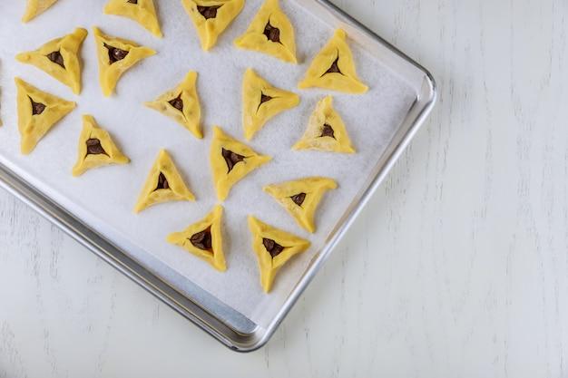 Ungekochte purim-kekse mit schokoladenstückchen auf weißem tisch.