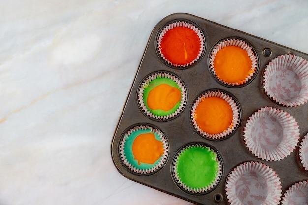 Ungekochte regenbogen-cupcakes auf zwei backblechen. ansicht von oben.