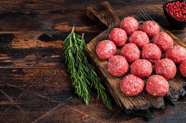 Ungekochte rohe fleischbällchen aus hackfleisch und schweinefleisch mit rosmarin. dunkler hölzerner hintergrund. draufsicht. speicherplatz kopieren.
