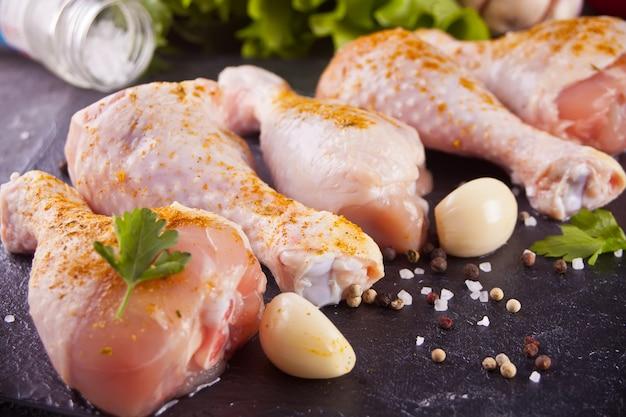 Ungekochte rohe hühnerbeine mit gewürzen und kräutern auf dem schwarzen behälter