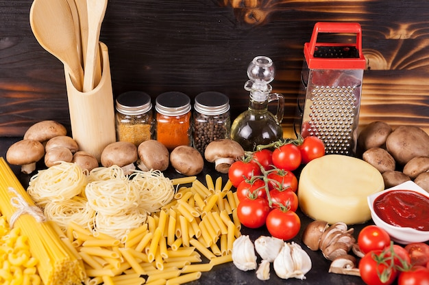 Ungekochte rohe makkaroni, nudeln und spaghetti neben frischem und gesundem gemüse, verschiedenen gewürzen und sonnenblumenöl auf dunklem rustikalem holzhintergrund