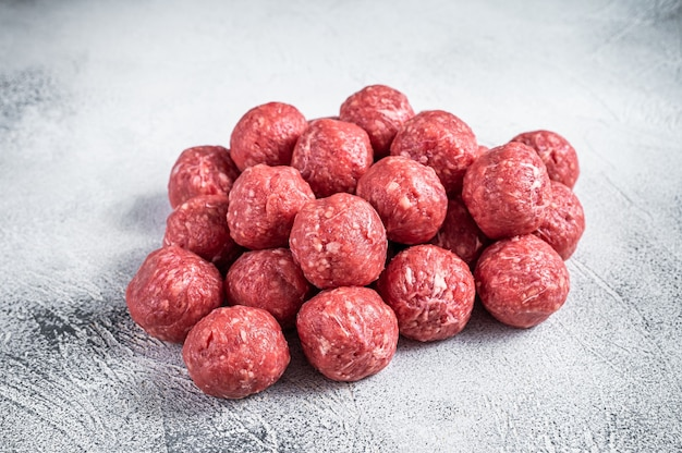 Ungekochte rohe rind- und schweinefleischbällchen stapeln sich