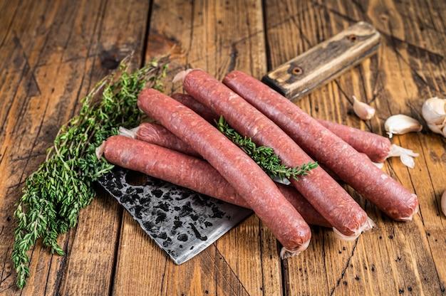Ungekochte rohe rind- und schweinswurst auf vintage-fleischerbeil. hölzerner hintergrund. draufsicht.