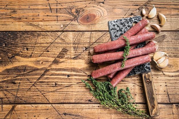 Ungekochte rohe rind- und schweinswurst auf vintage-fleischerbeil. hölzerner hintergrund.