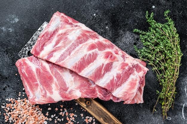 Ungekochte rohe schweinerippchen auf metzgerfleischbeil. schwarzer hintergrund. draufsicht.