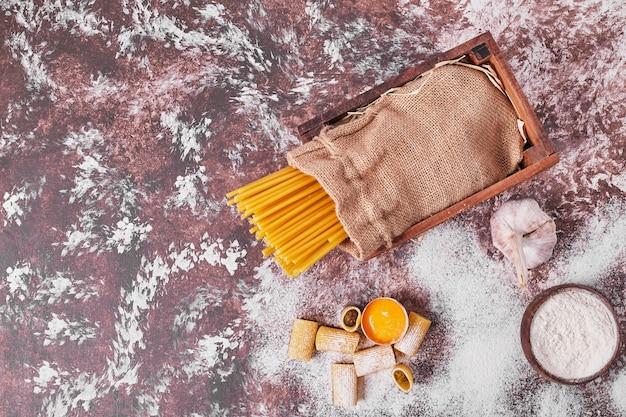 Ungekochte rohe spaghetti in einem sack auf holzoberfläche.