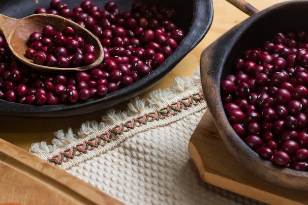 Ungekochte rote bohnen auf schwarzen tellern, schneidebrett und begleitet von petersilie