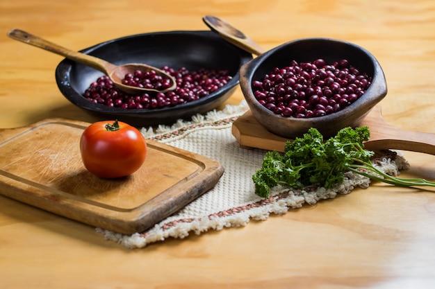 Ungekochte rote bohnen auf schwarzen tellern, schneidebrett und serviert mit frischen tomaten und petersilie