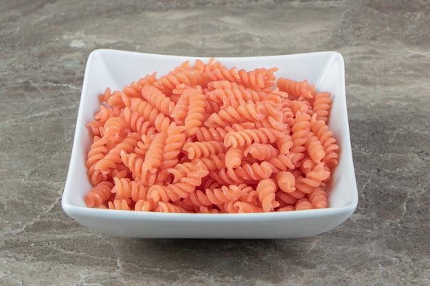 Ungekochte rote fusilli in weißer schüssel