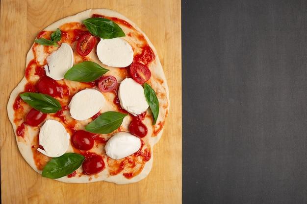 Ungekochte selbst gemachte pizza auf schneidebrett auf dunklem hintergrund