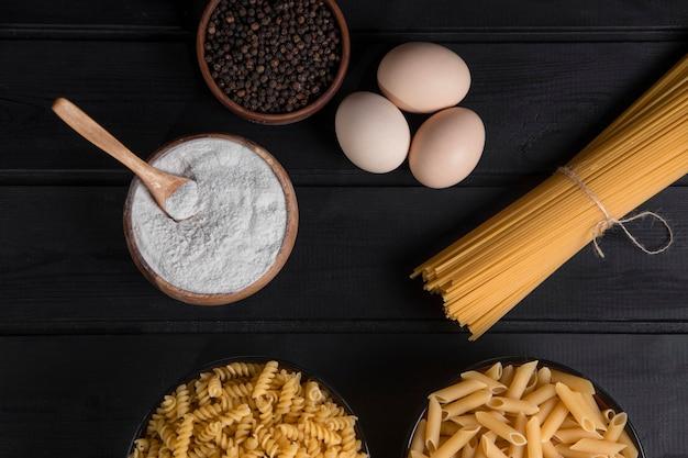 Ungekochte spaghetti mit seil und pfefferkörnern auf einem holztisch. hochwertiges foto