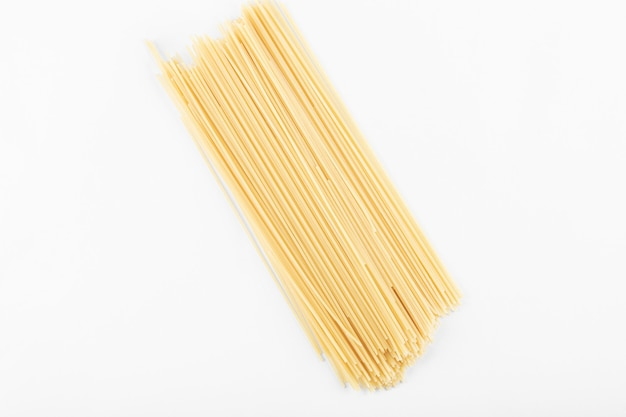 Ungekochte spaghetti-nudeln auf weißem hintergrund. foto in hoher qualität