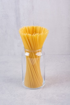 Ungekochte spaghetti-nudeln im glas