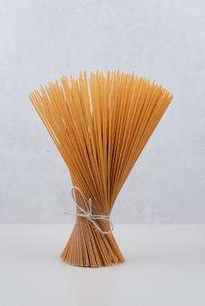 Ungekochte spaghetti-nudeln im seil auf weißer oberfläche