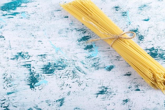 Ungekochte spaghetti-nudeln mit seil auf bunter oberfläche gebunden.