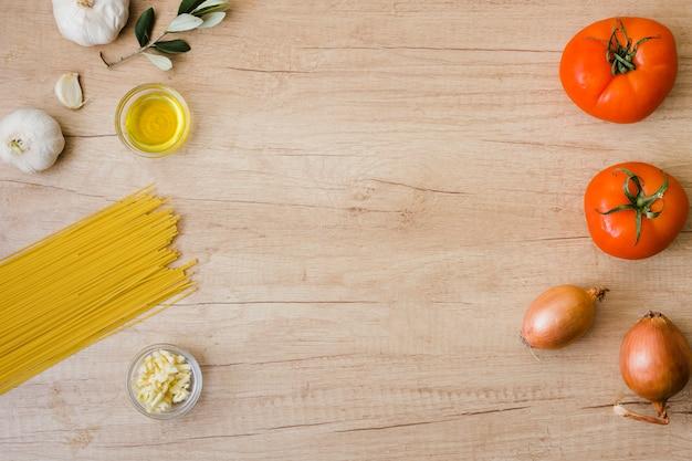 Ungekochte spaghetti; öl; knoblauch; zwiebel und rote tomaten auf hölzernem schreibtisch mit kopienraum für das schreiben des textes
