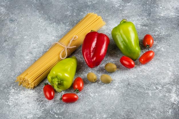 Ungekochte spaghetti und verschiedenes gemüse auf steinoberfläche.