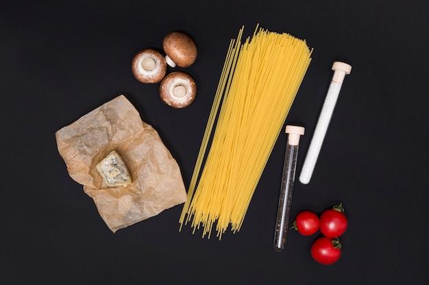 Ungekochte spaghettiteigwaren und vegetarischer bestandteil über schwarzem hintergrund