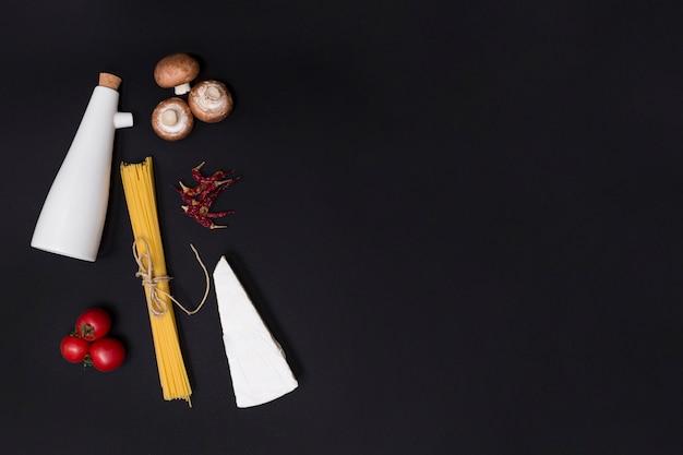Ungekochte spaghettiteigwaren und zutat über küchenoberteil