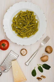 Ungekochte spinat-gemelli-nudeln mit käsereibe; gabel und zutaten auf hölzernen hintergrund