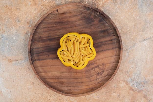 Ungekochte spiralmakkaroni mit pfeffer auf holzbrett