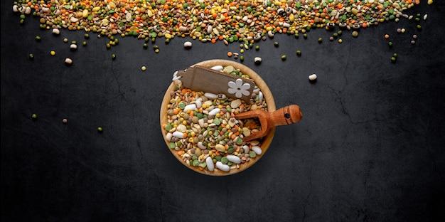Ungekochte suppe aus verschiedenfarbigen gemischten hülsenfrüchten mit gerste, dinkel, erbsen, bohnen, linsen und saubohnen auf dunklem hintergrund