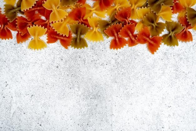 Ungekochte teigwaren auf konkretem hintergrund