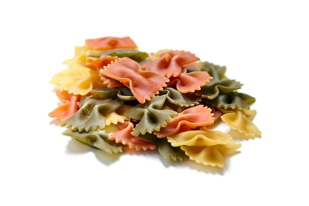 Ungekochte traditionelle italienische pasta der farfalle tricolore lokalisiert auf einem weiß